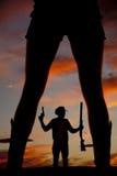 Silhouette d'un betwe haut de côté de regard de pistolet disponible de fusil de chasse de cowboy Photographie stock