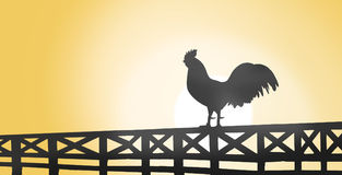 Silhouette d'un coq se reposant sur une barrière en bois sur la campagne Images stock