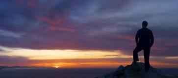 Silhouette d'un coucher du soleil admiratif d'homme Images stock