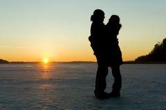 Silhouette d'un couple étreignant sur la glace Image libre de droits