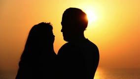 Silhouette d'un couple affectueux, baiser de la mer au coucher du soleil clips vidéos