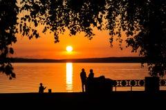 Silhouette d'un couple dans l'amour au coucher du soleil ou au lever de soleil Photos stock