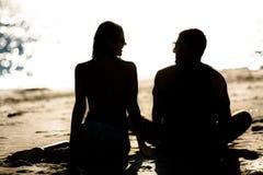 Silhouette d'un couple dans l'amour sur la plage au coucher du soleil Histoire d'amour Homme et une femme sur la plage Images libres de droits