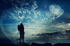 Silhouette d'un couple embrassant contre un ciel de coucher du soleil Photos libres de droits