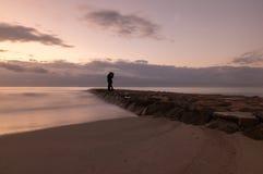 Silhouette d'un couple embrassant par la mer au lever de soleil Image libre de droits