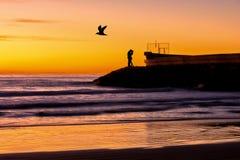 Silhouette d'un couple embrassant par la mer au lever de soleil Photo stock