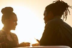 Silhouette d'un couple faisant un pain grillé pendant l'heure d'or Photographie stock libre de droits