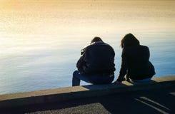 Silhouette d'un couple hétérosexuel se reposant au bord de la mer dans le southe des Frances images stock