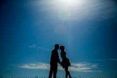 Silhouette d'un couple se penchant plus de pour embrasser Image libre de droits