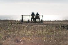 Silhouette d'un couple se reposant sur le banc près de l'océan Photographie stock libre de droits