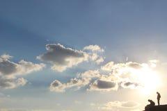 Silhouette d'un couple se tenant devant le coucher du soleil Photos libres de droits