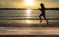 Silhouette d'un coureur Fonctionnement de femme sur la plage brouillée à l'arrière-plan image stock