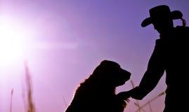 Silhouette d'un cowboy et de son crabot Images stock