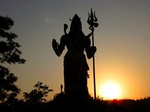 Silhouette d'un dieu indou Shiva au coucher du soleil Photo stock