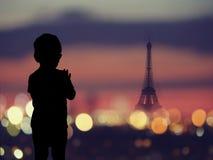 Silhouette d'un enfant à la fenêtre avec la silhouette de Tour Eiffel à Paris Photographie stock libre de droits