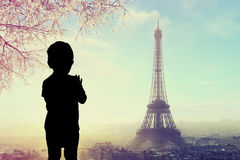 Silhouette d'un enfant à la fenêtre avec la silhouette de Tour Eiffel à Paris Photos libres de droits