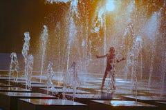 Silhouette d'un enfant jouant avec un pulvérisateur d'une fontaine un jour chaud d'été images stock