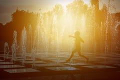 Silhouette d'un enfant jouant avec un pulvérisateur d'une fontaine un jour chaud d'été Photo libre de droits