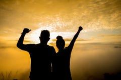 Silhouette d'un femelle et d'un mâle tenant des mains au lever de soleil Photos stock