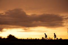 Silhouette d'un garçon jouant sur le fond de coucher du soleil Photos libres de droits