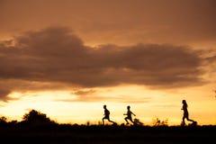 Silhouette d'un garçon jouant sur le fond de coucher du soleil Photographie stock libre de droits