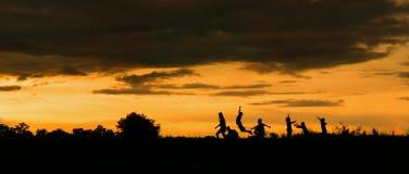 Silhouette d'un garçon jouant sur le fond de coucher du soleil Photographie stock