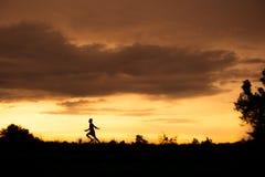 Silhouette d'un garçon jouant sur le fond de coucher du soleil Images stock