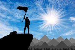 Silhouette d'un grimpeur sur un dessus de montagne avec un drapeau dans sa main Image stock