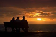 Silhouette d'un groupe d'aînés qui s'assied sur le banc Photographie stock