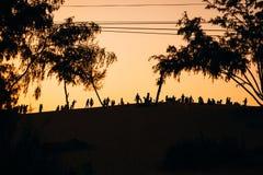 Silhouette d'un groupe de personnes amis se reposant sur le sable Photos stock