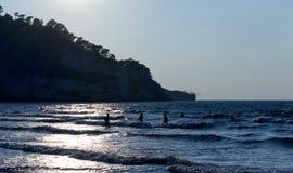Silhouette d'un groupe de personnes dans rétro-éclairé sur le bord de la mer ayant le bain Pour le concept de tourisme et de vaca Photos libres de droits