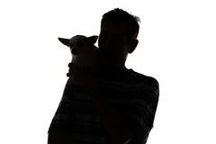 Silhouette d'un homme avec le chien Photos stock