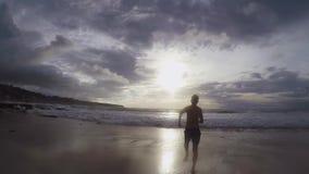 Silhouette d'un homme courant dans l'océan au coucher du soleil dans le mouvement lent banque de vidéos