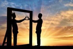 Silhouette d'un homme de narcissist et d'un geste de main d'un coeur par réflexion dans le miroir et la couronne sur sa tête Photo stock