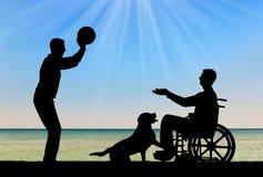 Silhouette d'un homme handicapé dans un fauteuil roulant jouant la boule avec un ami Photographie stock libre de droits