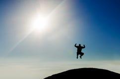 Silhouette d'un homme heureux sautant sur le dessus de montagne Image stock