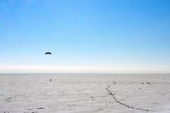 Silhouette d'un homme kiting dans l'horaire d'hiver au lac congelé Images libres de droits