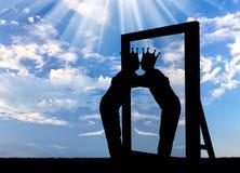 Silhouette d'un homme narcissique avec une couronne sur sa tête étreignant sa réflexion dans le miroir Photos stock