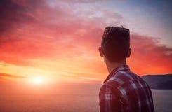 Silhouette d'un homme observant le coucher du soleil sur la plage Image stock