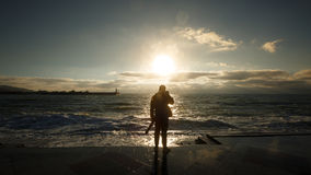 Silhouette d'un homme photographiant la vague Le photographe de touristes tire la mer orageuse sur le remblai humide Photo libre de droits
