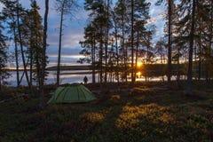 Silhouette d'un homme près d'une tente sur le rivage de lac Images stock