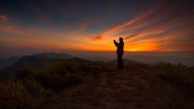 Silhouette d'un homme prenant la photo Photos stock