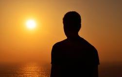 Silhouette d'un homme regardant le coucher du soleil Image libre de droits