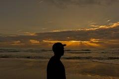 Silhouette d'un homme regardant le lever de soleil gentil Photos stock