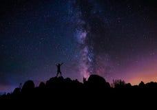 Silhouette d'un homme se tenant sur une colline, avec la manière laiteuse Photos stock