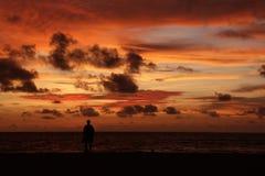 Silhouette d'un homme solitaire sur une plage au crépuscule image stock