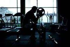 Silhouette d'un homme sportif établissant au gymnase Photographie stock