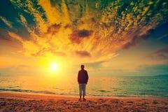 Silhouette d'un homme sur la plage regardant le coucher du soleil Photo stock