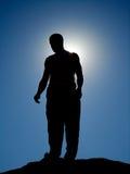 Silhouette d'un homme sur les roches Photographie stock libre de droits