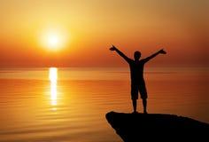 Silhouette d'un homme sur un dessus de montagne sur le coucher du soleil Images libres de droits